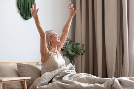 Happy older woman sitting in comfortable bed, stretching hands after awakening in bedroom, happy satisfied older female doing easy exercise in the morning, greeting new day, sunrise