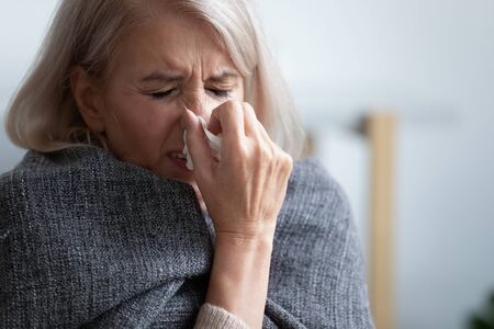 Nieszczęśliwa dojrzała kobieta przykryta kocem źle się czuje, kicha z bliska, trzyma chusteczkę, cierpi na gorączkę, reakcję alergiczną lub sezonową infekcję, zdenerwowana przygnębiona starsza kobieta płacze