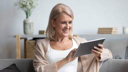 Smiling mature woman using computer tablet apps, reading good news in social network, happy older female sitting on couch, holding electronic device, looking at screen, shopping or chatting online