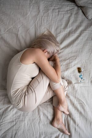 Depressed mature woman lying in bed with bottle of pills top view, crying and thinking, unhappy older female suffering from insomnia or depression, psychological problem, overdose concept