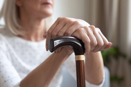 Mature woman holding hands on wooden cane close up, disabled older female sitting alone indoors, using walking stick during rehabilitation, older people healthcare nursing home concept Stockfoto