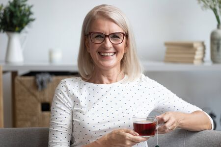 Head shot portrait smiling mature woman holding cup of black tea with tea bag inside, mature female sitting on couch, relaxing at home, drinking enjoying hot beverage in mug in the morning