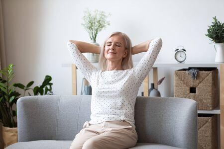 Happy relaxed older woman with closed eyes sitting leaning back on couch, calm mature female with hands behind head enjoying weekend, stretching on couch, resting and daydreaming, no stress concept