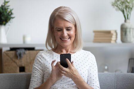 Glimlachende volwassen vrouw die telefoon vasthoudt, apps voor mobiele apparaten gebruikt, naar het scherm kijkt, gelukkige oudere vrouw die online chat, sms't, bericht op mobiele telefoon schrijft, thuis plezier heeft, op de bank zit Stockfoto