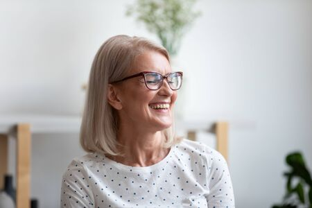 Close up happy beautiful mature woman wearing glasses laughing at funny joke, older female with healthy toothy smile having fun at home, enjoying weekend at home, excited by good news