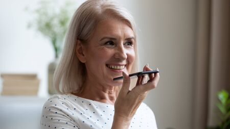 Smiling mature woman recording voice message on phone close up, happy older female chatting online or speakerphone, activating digital assistant on smartphone, holding cellphone in hand
