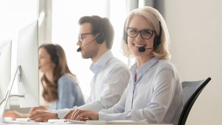 Call center old worker wearing glasses use telephone with headset and computer sitting at workplace pose for camera millennial associates working on background, friendly service phone operator concept