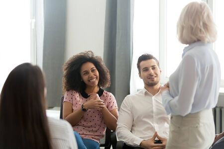 Diverse millennial trainee interns students sitting on office chairs listens old business coach, different ages ethnicity workers associates having informal friendly talk take break at workday concept