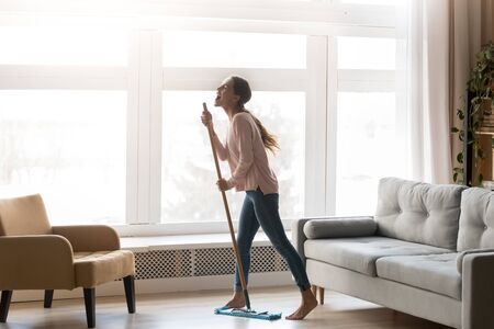 Funny happy young woman holding mop microphone singing song in modern living room interior with big window, carefree active funky girl having fun cleaning floor at home enjoying housework alone Stock fotó