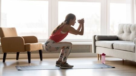 Sporty young woman doing squat morning exercise alone in living room, serious fit girl wearing sportswear crouching training muscles workout at home for healthy body lifestyle concept, side view Reklamní fotografie