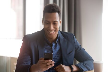 Smiling african businessman using phone in office, happy black man entrepreneur hold smartphone work with business application texting sms at workplace, corporate technology and digital communication Banco de Imagens - 131245223