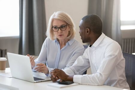 Serious experienced aged businesswoman in glasses explains help to african new employee task usage of corporate online program sitting at table office room working together, mentor and trainee concept