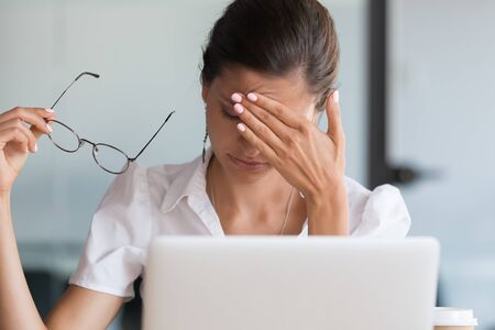 Stressed young business woman holding glasses feeling headache, overworked upset lady suffer from eye strain or migraine coping with dizziness blood pressure tired of computer work syndrome concept