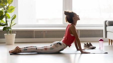 Calm mindful woman practising yoga asana at home, young healthy yogi girl doing urdhva mukha svanasana upward facing dog pose exercise stretching muscles indoors after fitness training concept