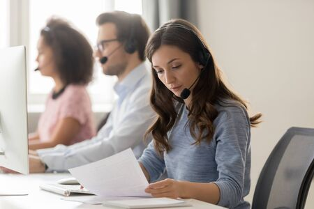 Telemarketing representative or sales agents sitting at workplace wearing headset use computer, focus on call center member millennial female read document paper, helpline office, busy workday concept