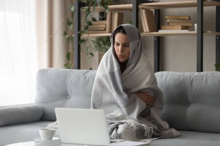 Sick ill young woman feel cold covered with blanket sit on sofa watching movie on laptop, annoyed girl shiver freezing warming at home wrapped with plaid, no central heating problem and flu concept 스톡 콘텐츠