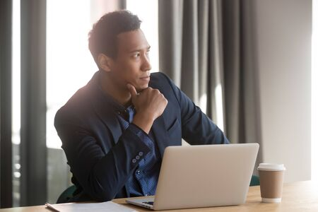 Thoughtful african businessman holding hand on chin looking away lost in thoughts at work, serious doubtful black entrepreneur think of problem business challenge sit at office desk with laptop