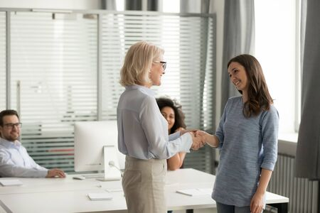 In coworking modern shared room gather diverse employees looks at company ceo handshake with month best worker young shy woman lady boss feels gratitude express praise telling compliment to specialist