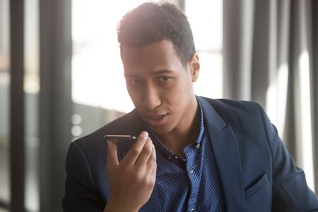 Serious african businessman hold phone speak activate virtual digital voice assistant on smartphone at work, black man ask internet assistance service make call in office mobile ai technology concept Stock fotó