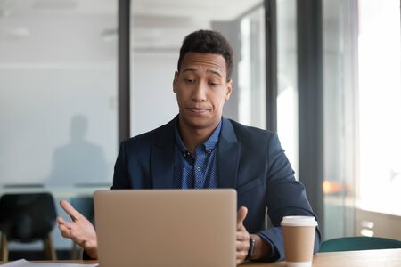 Stressed annoyed african black business man using stuck slow laptop upset about broken computer problem, frustrated by application error, system virus data loss on pc, website mistake at workplace Фото со стока