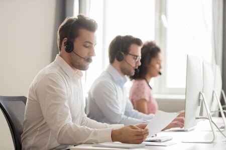 Diversi lavoratori del call center seduti in fila nella stanza condivisa che indossano le cuffie usano il computer, si concentrano sul ragazzo in possesso di documenti di lettura della carta, sul processo di vendita e sul concetto di linee guida per il supporto dell'assistenza clienti