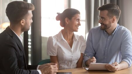 Smiling young couple thinking ready to sign contract making decision meeting bank manager insurer, family clients consider insurance mortgage real estate loan offer meeting broker realtor in office
