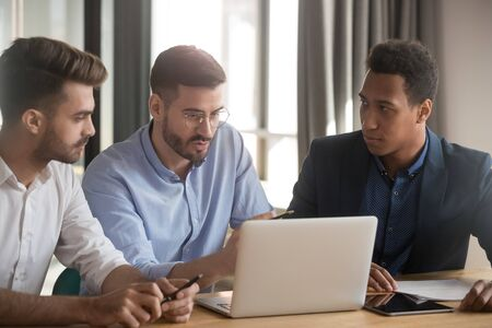 Serious mentor leader coach and diverse business men team discuss online project at meeting, multiracial male colleagues looking at laptop listen to teacher instruct explain computer work in office Stock Photo