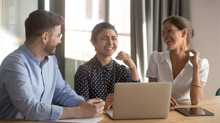 Three happy diverse coworkers talking laughing at funny joke working together in teamwork with laptop, cheerful friendly indian and caucasian staff mates having fun cooperating at workplace in office