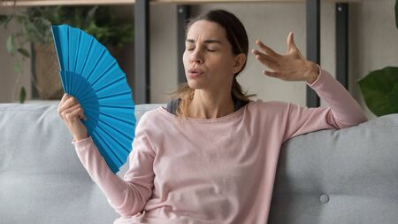 Stressed sweaty young woman holding waving fan suffer complain on heat at home, overheated annoyed girl sweating feel uncomfortable hot in summer weather problem without air conditioner in apartment Фото со стока