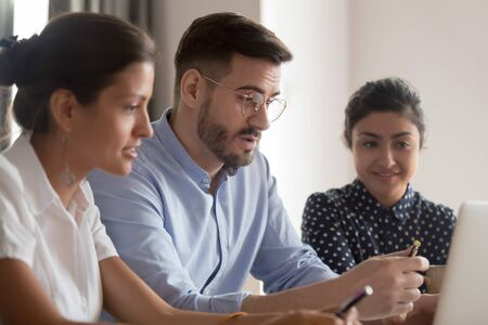 Serious male caucasian teacher mentor coach instructing diverse trainees students explaining computer project, leader teaching indian intern looking at laptop talking to employees sit at office desk