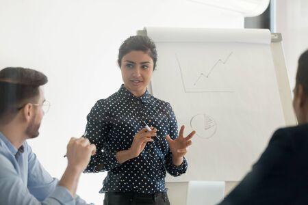Entrenador de conferenciante indio femenino confiado que capacita al grupo de empleados diversos dar presentación de rotafolio en la reunión de la oficina, presentador de mujer de negocios hindú enseña al equipo del personal en el taller corporativo Foto de archivo