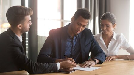 Young mixed race ethnicity family couple customers clients sign mortgage loan contract write signature on sale purchase agreement take loan buy insurance meeting bank agent make financial deal Stockfoto