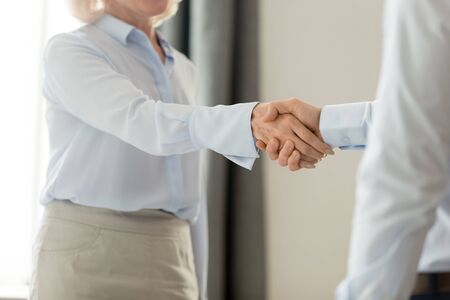 Cropped close up image middle aged business lady greeting corporate client shake hands company partner or investor, handshake symbol of regard respect first impression meeting and acquaintance concept Banco de Imagens - 131245253