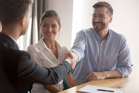 Happy young couple or hr team handshake lawyer broker job applicant make business deal at meeting interview, family clients shake hand of insurer thanking for consulting buying insurance services