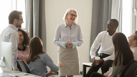 Lachende oude coach teamleider praten met diverse collega's chatten op zakelijke bijeenkomst, vriendelijke multiraciale kantoormedewerkers en vrouw van middelbare leeftijd ceo hebben een leuk gesprek bij koffiepauze concept