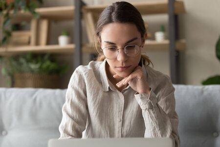 Focused serious thoughtful female student freelancer looking at laptop screen solving problem thinking of creative idea working studying on computer doing freelance side job sit on sofa at home