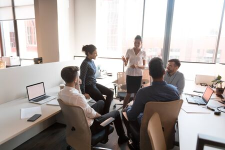 Multiethnische Geschäftsteamleute, die beim Briefing der Unternehmensgruppe Ideen austauschen, weibliche Mentor-Coach-Leiterin im Gespräch mit Arbeitern, die Praktikanten ausbilden, unterrichten bei der Bürositzung über die Projektstrategie