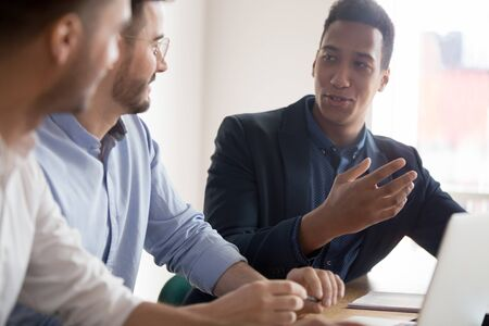 African businessman offering idea at diverse team meeting, three male colleagues talking collaborating on project in office, business men group mentor interns discuss corporate strategy work together Stock Photo - 131245500