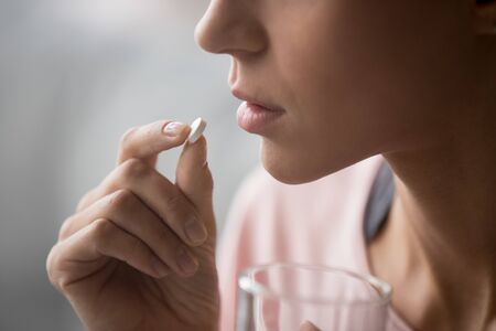 Sick ill woman holding antidepressant painkiller antibiotic pill glass of water take medicine, female handing tablet meds to mouth to relieve pain, health care medicament concept, close up side view 스톡 콘텐츠