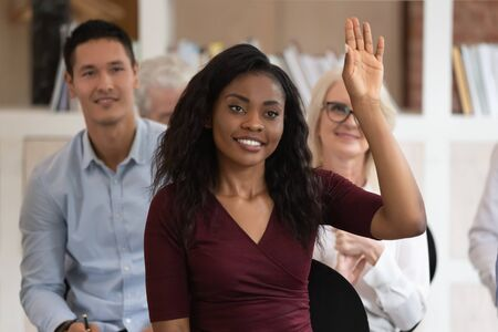 Smiling african American female leader raise hand answer question at team training in office, happy confident black woman employee volunteer participate in company business seminar. Leadership concept