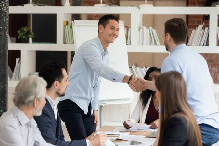 Smiling multiracial colleagues handshake greeting at business meeting in office, happy male employees shake hand get acquainted at briefing, coworkers congratulate with success or promotion Stockfoto