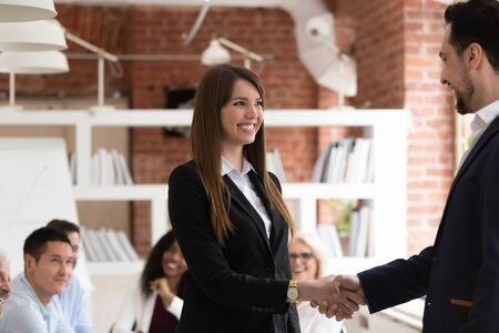 Smiling businessman handshake excited female employee congratulating with personal business success, happy employees businesspeople shake hands greeting get acquainted at office briefing or meeting Фото со стока - 131271629