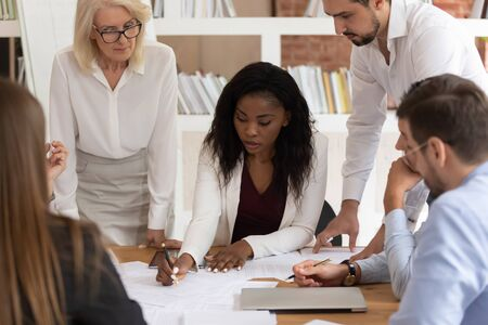 Focused african American businesswoman explain discuss paperwork project with diverse colleagues, concentrated businesspeople brainstorm considering financial business plan collaborating at briefing Stockfoto