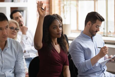Focused african American female employee raise hand volunteer answer question at team training in office, motivated black woman worker participate in teambuilding activity at business seminar Imagens