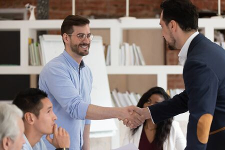 Excited male businesspeople handshake congratulate with promotion success at company office meeting, smiling colleagues employees shake hand greeting get acquainted at briefing. Acquaintance concept