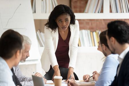 Serious millennial african American businesswoman head office briefing talk with employees, focused black female ceo or boss lead meeting with coworkers brainstorm discuss company plans ideas