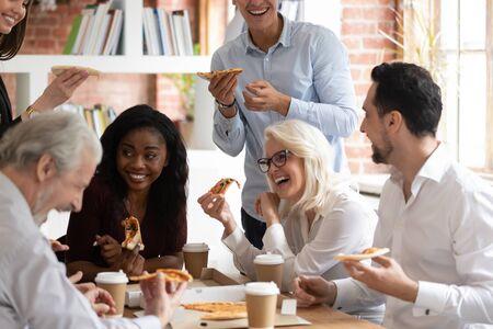 Rozradowany wielorasowy pracownik dobrze się bawi, jedząc pizzę pijąc kawę w biurze, uśmiechając się, szczęśliwi, różnorodni koledzy mają przerwę na lunch, śmiejąc się, delektując się włoskim fast foodem z dostawą na wynos