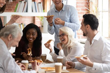 Un employé multiracial ravi s'amuse à manger de la pizza en buvant du café au bureau ensemble, souriant heureux divers collègues prenant une pause déjeuner en riant en profitant de la livraison de plats à emporter italiens
