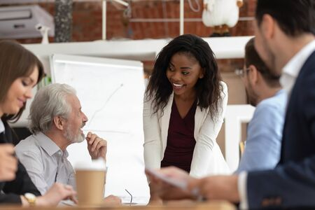 Happy black young female boss stand leading company meeting talk brainstorming with diverse coworkers, smiling african American millennial businesswoman speak head briefing collaborating with workers Stock Photo