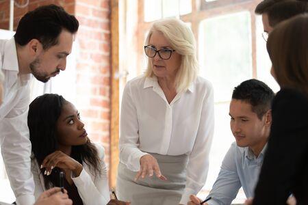 Empresarios multirraciales motivados se reúnen para hablar sobre el proyecto empresarial en una reunión de la empresa, colegas de empleados diversos y exitosos que colaboran juntos en una sesión informativa para intercambiar ideas Foto de archivo